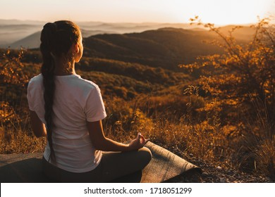Woman meditating alone on hill with amazing autumn mountain view at sunset. Zen spiritual concept. Praying alone, harmony with nature.