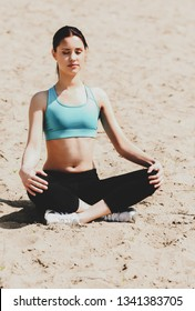Woman meditating at the beach in lotus asan in sunny day.