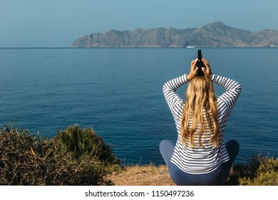 Woman is meditating with bottle of beer on head above sea