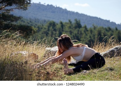 Woman meditating and doing yoga on the top of a mountain in nature