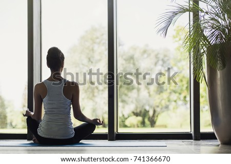 Woman meditating at home. Girl practicing yoga in class