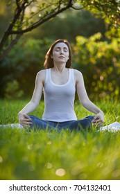 Woman meditating in lotus pose at the beautiful park
