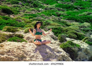 Woman meditating in Lotus pose on the rocks. the concept of rest, relaxation, spiritual peace, yoga