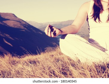 Woman Meditating in Lotus Position on Top of a Mountain