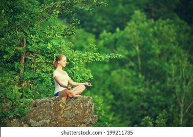 woman meditating in lotus posture, doing yoga on top of the mountain on a rock in nature in the forest