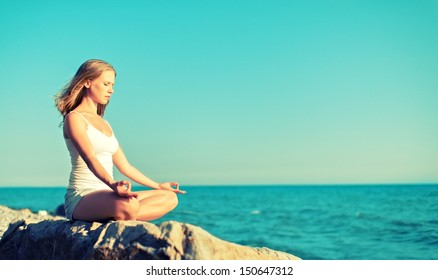 woman meditating in  lotus yoga on  coast of  sea on the beach