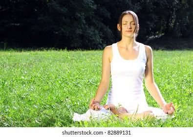 Woman meditating in nature, exercising yoga