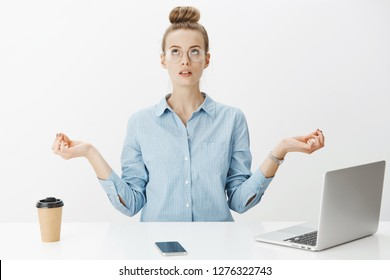 Woman meditating in office sitting near table having break from writing article in laptop, drinking coffee looking up practicing yoga, making nirvana orbs with hands spread aside over gray wall