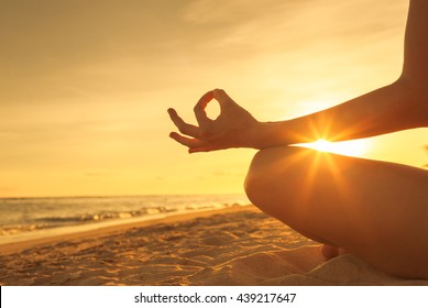 Woman meditating on the beach.