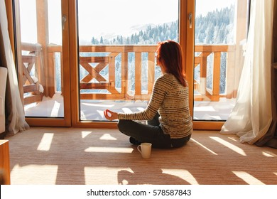 Woman meditating on floor at home and looking through window at snow covered mountain.