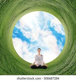 Woman meditating on green field in circle