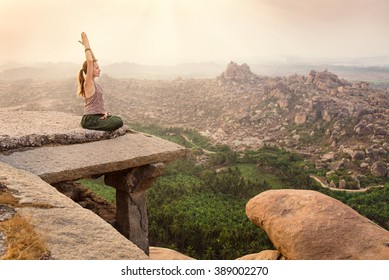 Woman meditating on rocky background on sunrise in Hampi, India