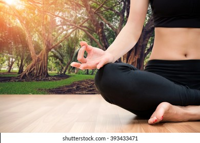 woman meditating on wood floor with garden background
