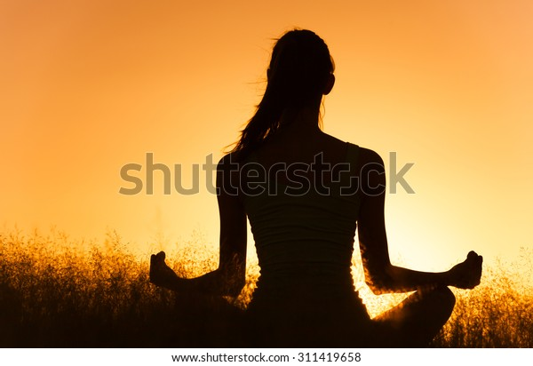 Woman meditating in the park.