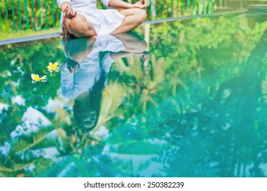 Woman meditating at pool side. Reflection in the water (focus on two floating flowers)