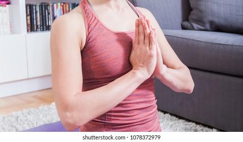 Woman Meditating and Practicing Yoga, lotus pose namaste gesture, ardha padmasana exercise, relax at home, healthy lifestyle