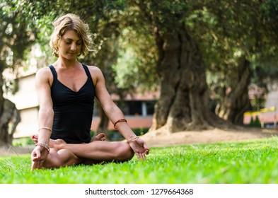 Woman Meditating And Practicing Yoga, Lotus Pose, Padmasana. Meditation On Sunny Autumn Day At Park. Workout Outdoor.