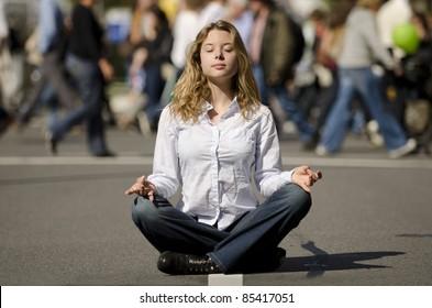 woman meditating yoga in lotus position on busy urban street