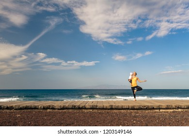 Woman meditating in yoga pose holding baby toddler. Life balance concept, ocean view, beach and wooden sidewalk. Motivation and inspirational summer sea landscape. Healthy lifestyle outdoors.