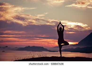 Woman meditating in yoga pose silhouette at the ocean, beach and the mist mountains. Sunrise. Motivation and inspirational exercising. Healthy lifestyle outdoors in nature, fitness concept.