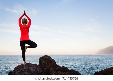 Woman meditating in yoga vrksasana tree pose silhouette at the ocean, beach and rock mountains. Motivation and inspirational fit and exercising. Healthy lifestyle outdoors in nature, fitness concept.