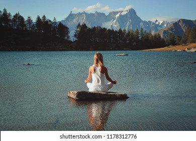 Woman meditation in mountain lake. Lotus asana