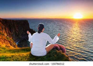 Woman at meditation on the edge of  Irsih cliffs