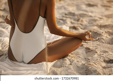 Woman meditation on the nature concept. Close-up view on hands and back. Young beautiful woman in bikini meditating and listening to calm music in yoga lotus pose on deserted tropical beach outdoors