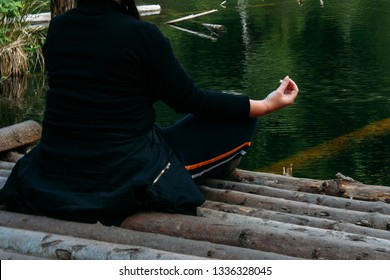 Woman in a meditative yoga position sit on wooden pontoon on the lake