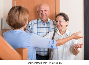 Woman meeting mature friends at the door