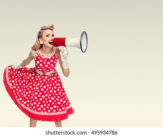 Woman with megaphone dressed in pinup style red dress in polka dot and white gloves. Caucasian blond model in retro fashion vintage studio shoot. Copyspace area for advertising slogan or text message.