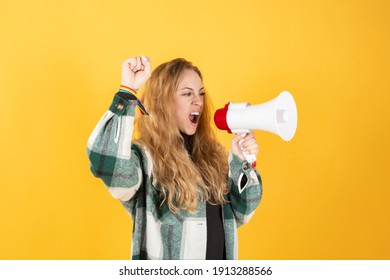 woman with megaphone screaming fighting for her feminist rights, yellow background