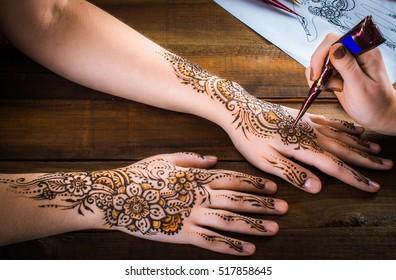 woman mehendi artist painting henna on the hand