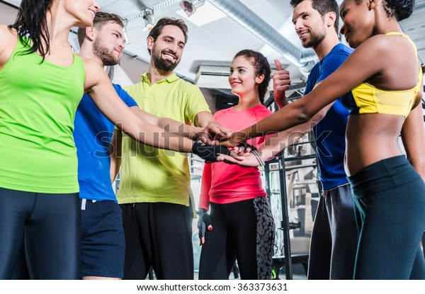 Woman and men being motivated for fitness and sport stacking their hands