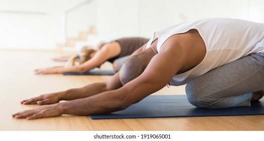 Woman and men performing stretching between asanas during group yoga training at gym. Fitness and Hatha yoga concept