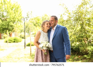 Woman and men posing in park. Beautiful couple. Woman with bouquet of white flowers