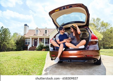 Woman and men sitting in trunk with tablet and smiling.Couple in car with computer discovering Internet,social media, planning trip,spending time together.Vehicle near house in suburban neighborhood.
