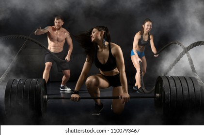 Woman and men working out with battle ropes at gym