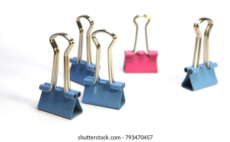 Woman and men in the workplace (leader or harrassment) concept illustrated with pink and blue bulldog clips