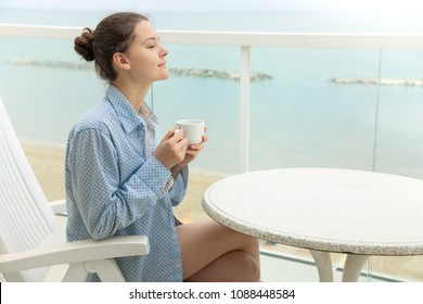 Woman in men's shirt drinking coffee in home terrace