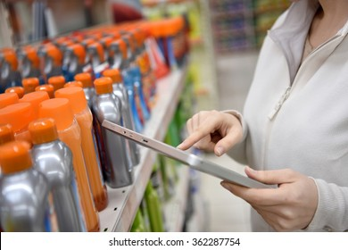 Woman merchandiser checking products available with digital tablet
