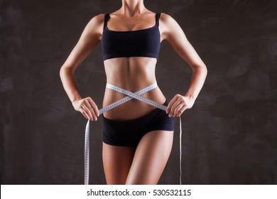 Woman mesuring her waist