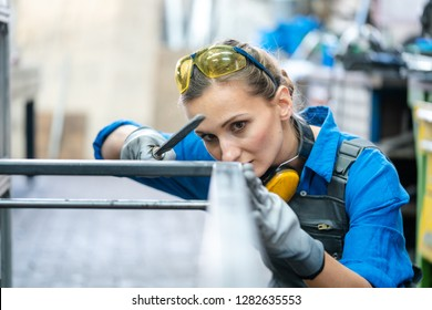 Woman metalworker checking the accuracy of her work holding steel file in her hand