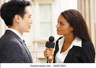 A woman with a microphone interviews a well dressed man. Could be politician, business or other professional.