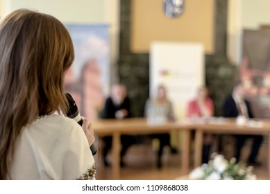 A woman with a microphone performs at a round table meeting. The photo is out of focus