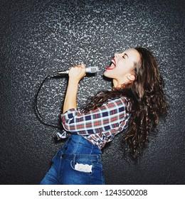 Woman with microphone singing - indoor studio portrait