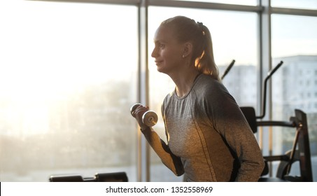 Woman of middle age working out in gym. Healthy lifestyle.Training on exercise machine.