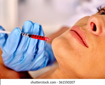 Woman middle-aged in spa salon with beautician. Botox injections.