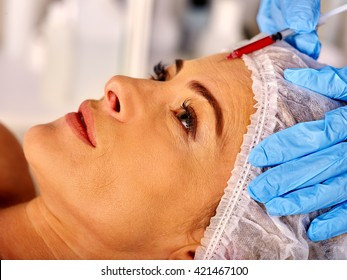 Woman middle-aged in spa salon with beautician. Beauty woman giving anti-aging injections. Facial injections.