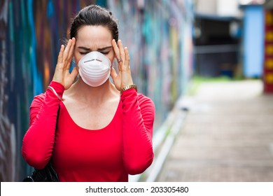 A woman with migraine or headache wearing a face mask